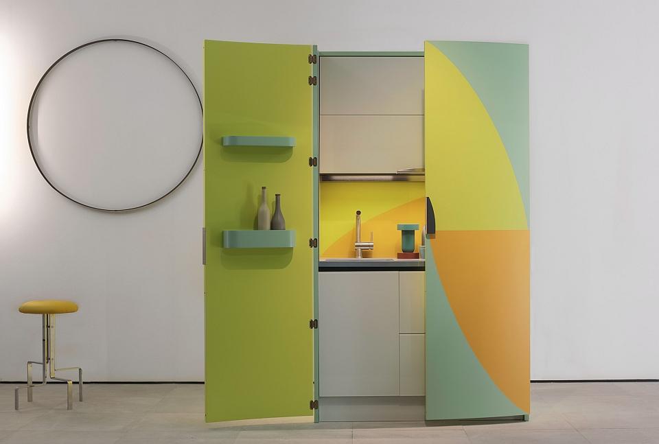 カーブを描いたカラフルな木製キャビネットの内側にキッチンが隠れたAM01