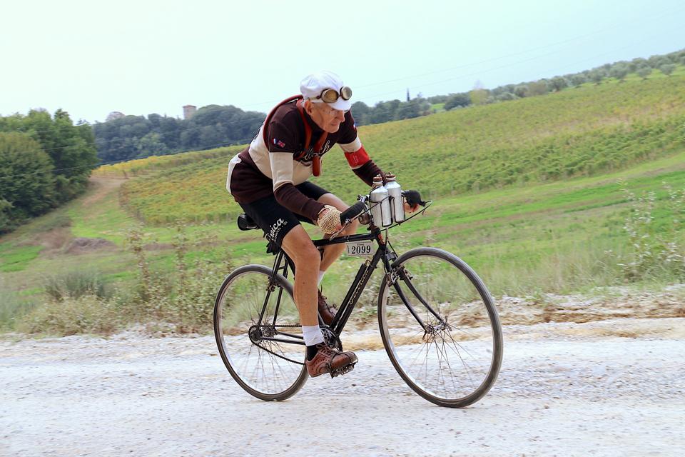 ヴィンテージ風コスチュームを着て自転車で坂道を駆け上る年配の外国人男性
