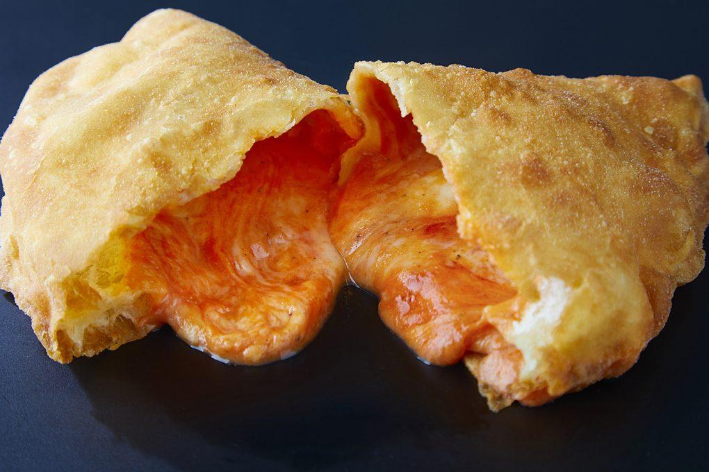 二つにカットされたところからチーズが溢れ出すパンツェロット