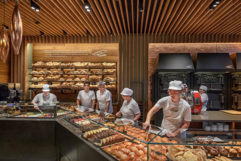 店内で商品のパンを陳列するスタッフとそれを眺めるプリンチ氏