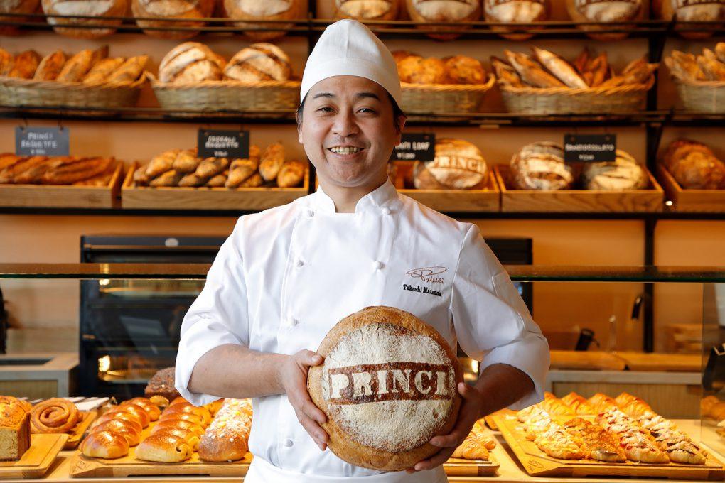 プリンチの文字が書かれた大きなパンを持つヘッドシェフの松田武司氏