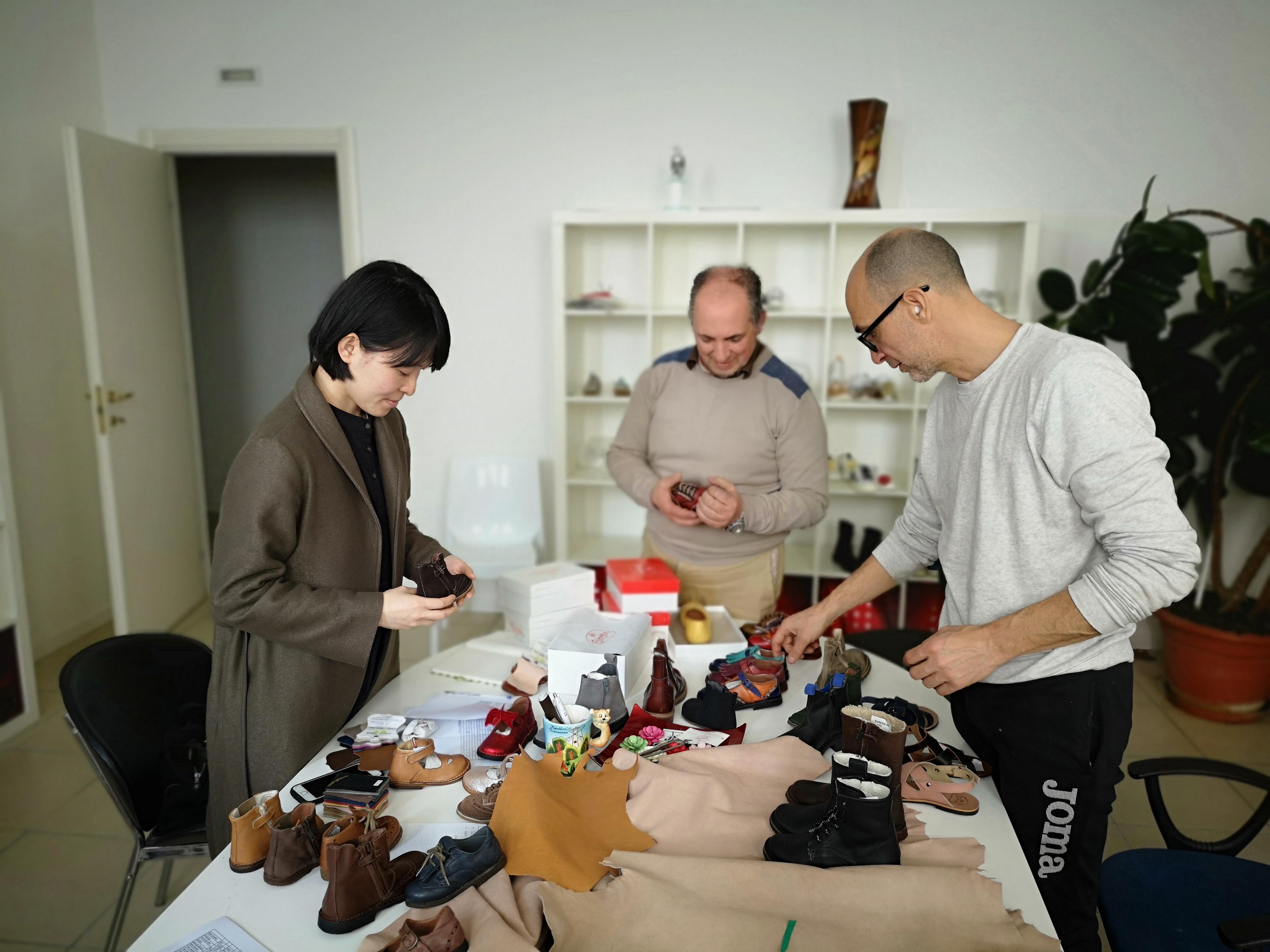 卓を囲みイタリア人二人と一緒に商品を見定める小川美佳さん
