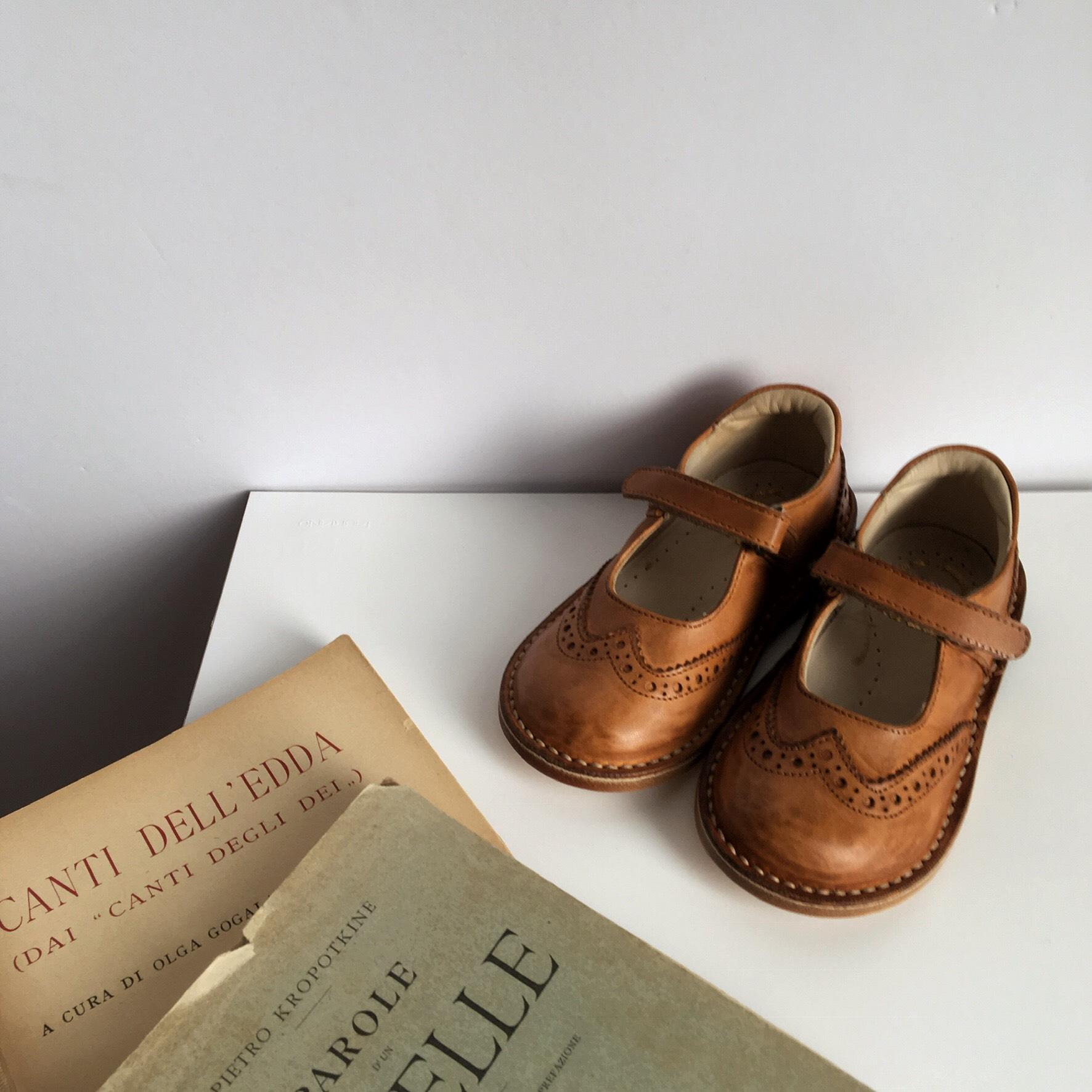 机の上にイタリア語の本と並べられたさんが販売する革靴