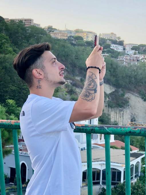 ナポリのビュースポットでナポリ湾を撮影する「家族」と日本語で刺青を入れた若者