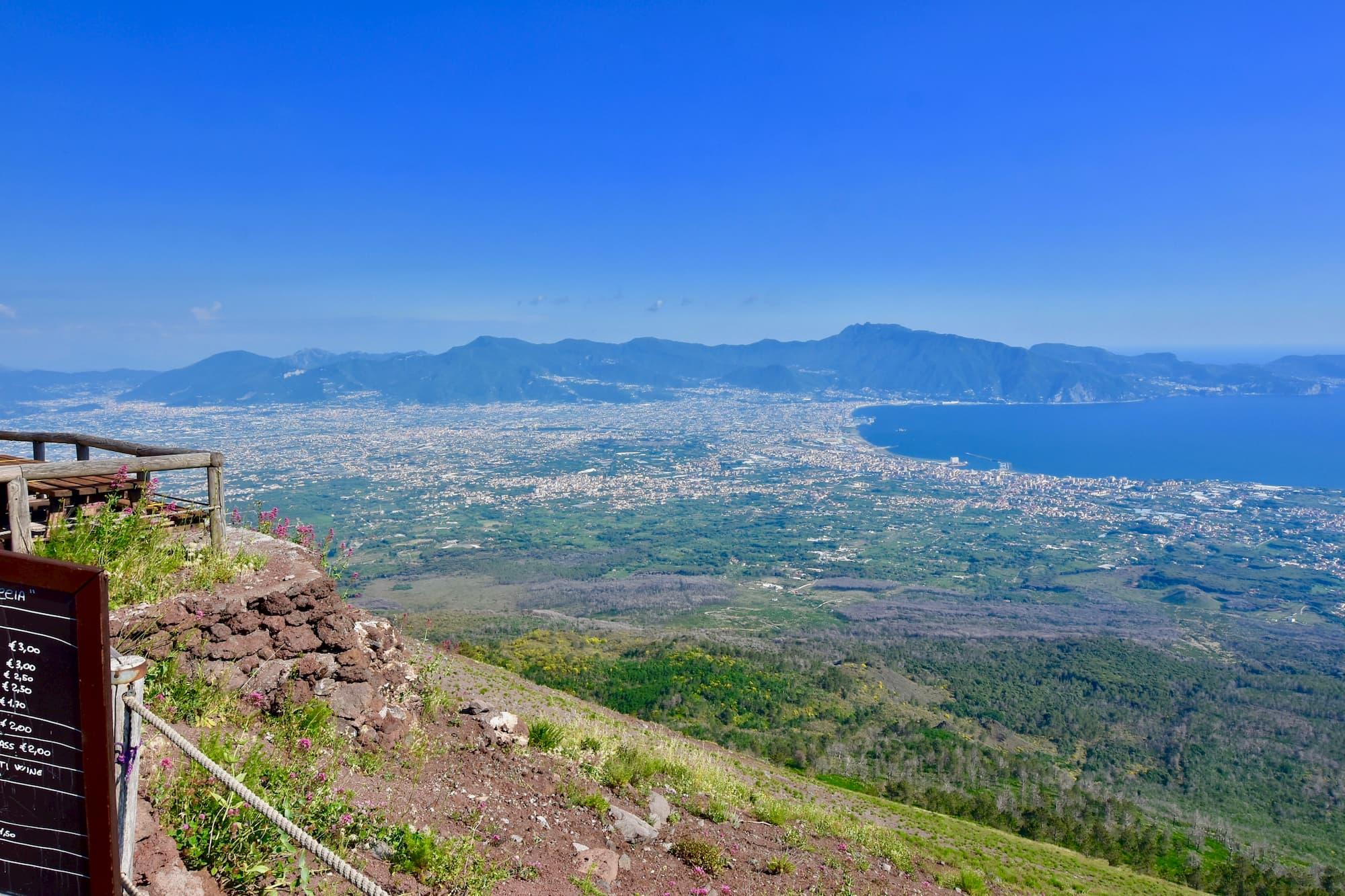 ヴェスヴィオ山頂からみえるポンペイ遺跡(写真ほぼ中央の緑に囲まれた茶色い部分)。バールのメニューには、ヴェスヴィオ近郊の有名なワインラクリマ・クリスティ・ディ・ヴェスビオもあった。