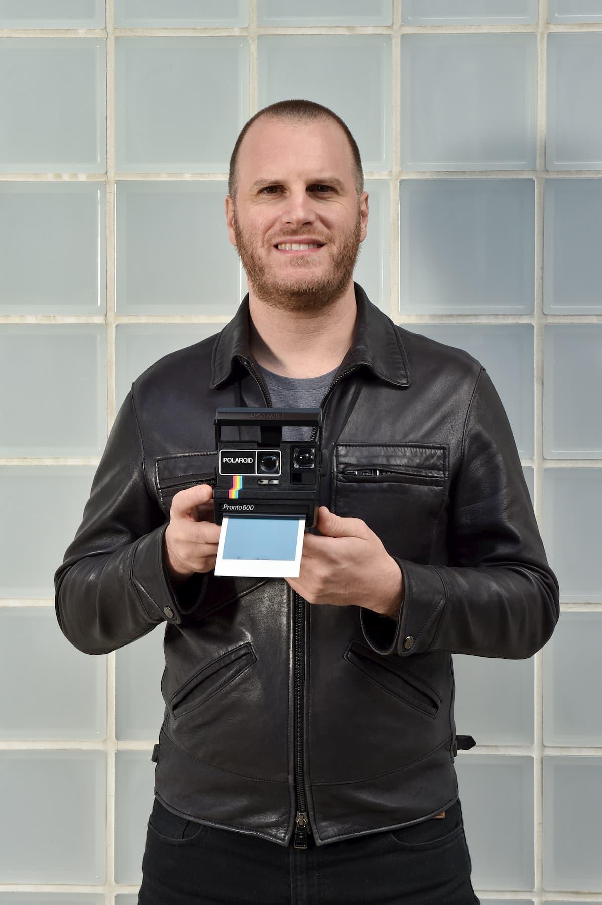 ポラロイドカメラを持つマルコさん