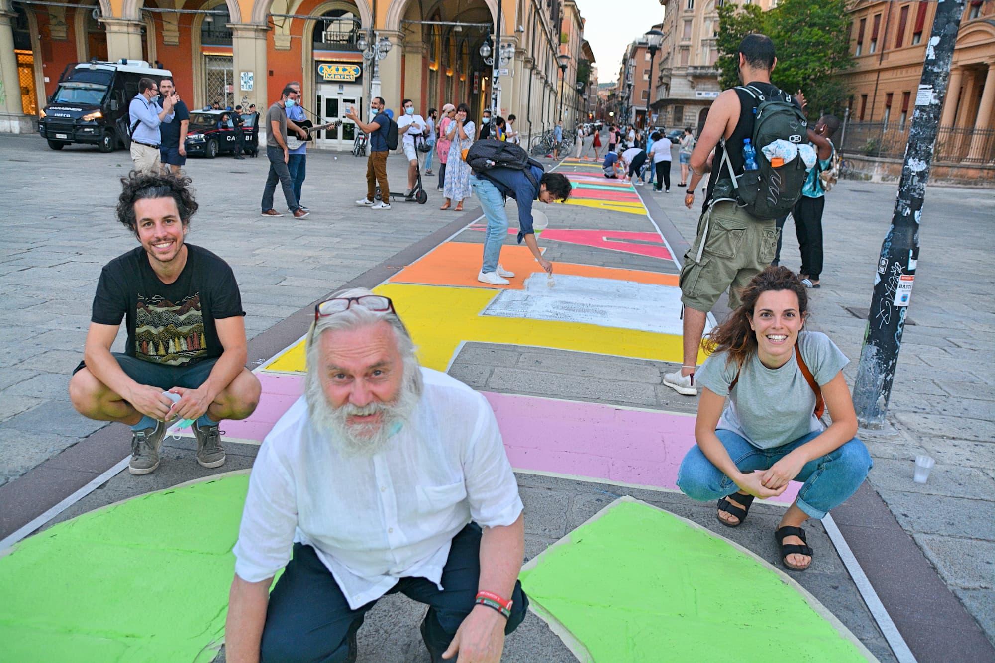 広場には「イワシ運動」発起人のMattia Santori(マティア・サントーリ)さん(写真左)とGiulia Trappoloni(ジュリア・トラッポローニ)さん(写真右)に加え、貧困者支援のための食堂「Cucine Popolari(クッチーネ・ポポラーリ)」の主催や、副代表を務めるホームレス支援団体「Piazza Grande(ピアッツァ・グランデ)」などの活動により、昨年イタリア共和国のマッタレッラ大統領からコンメンダトーレという功労勲章を授与されたRoberto Morgantini(ロベルト・モルガンティーニ)氏も参加。