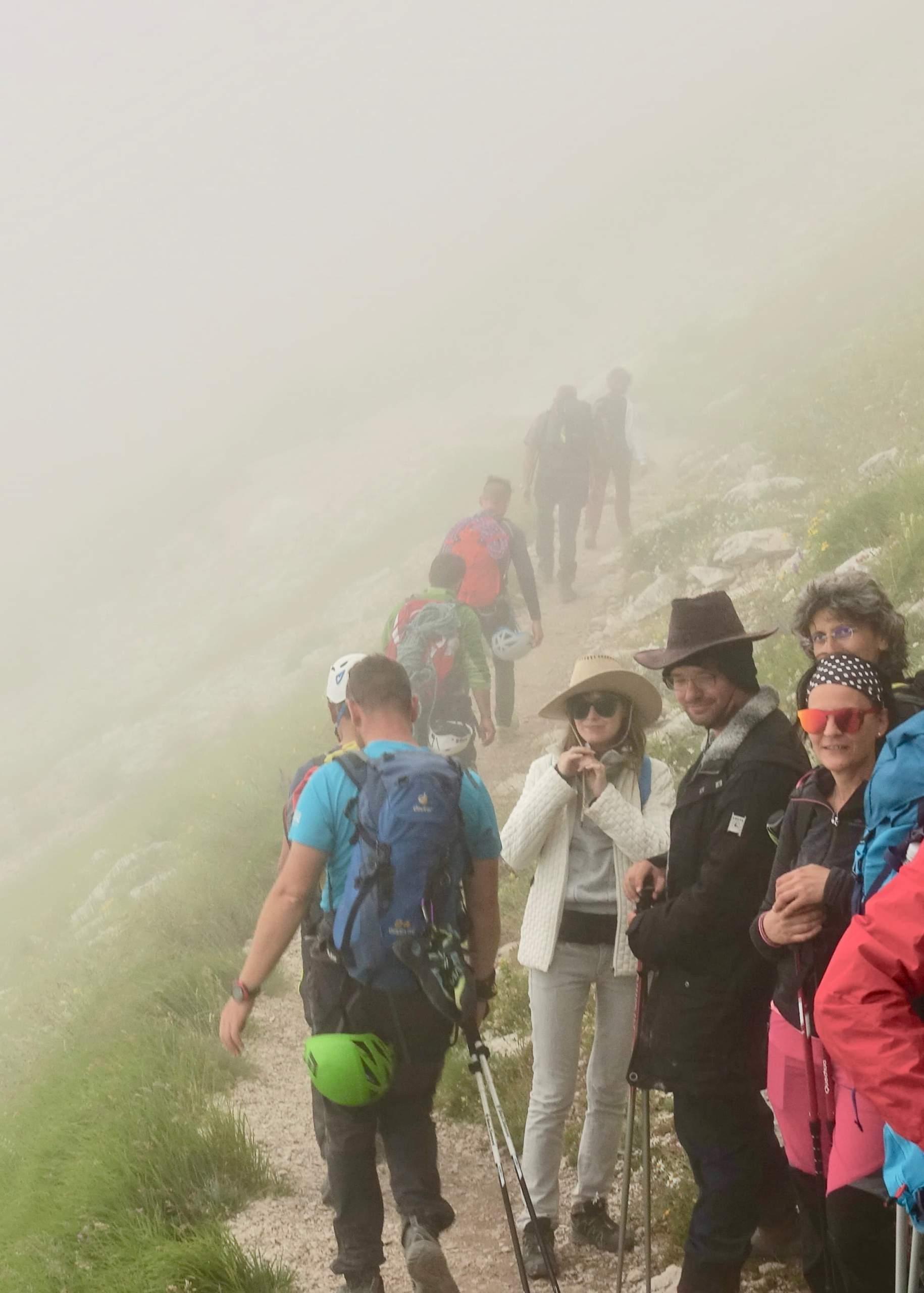 コルノグランデの山頂への登頂を終え、ロープ、ボルダリング用シューズ、ヘルメットなどを抱えて下山する若い男性グループ