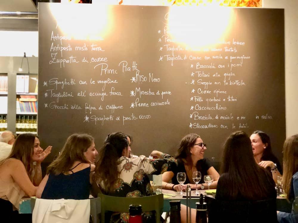 シックに装い、ワインも飲んでセラータを楽しむ若い女性たち(リヴォルノ)