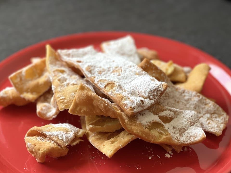 カーニバルの季節に売られる最もポピュラーな揚げ菓子。たっぷりの粉砂糖がかかっています。