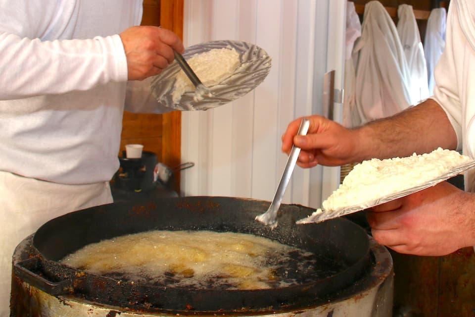 お米から作った生地を専用の円盤で広げたあと、専用のスプーンですくって鍋の中に落としていきます。