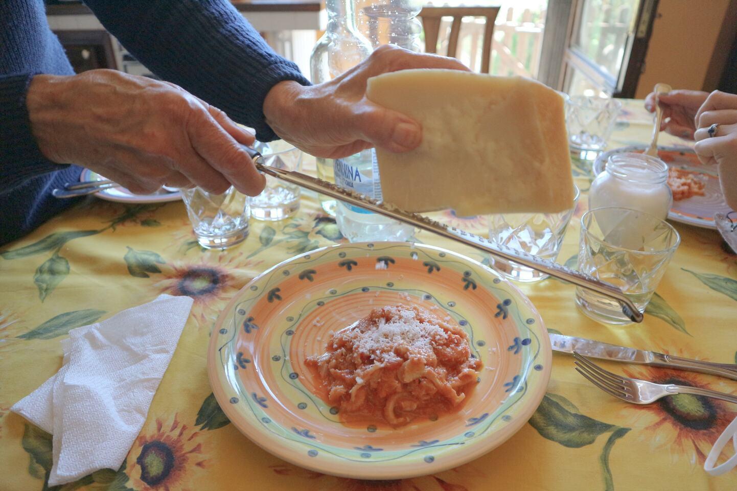 お皿にのせたトリッパにチーズを加えるところ