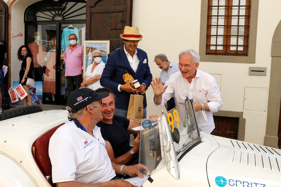BMW 328(1938年)を駆るラリードライバー、ニコラ・カルダーニ(左から2人め)を、地元ファンが待ち受けます