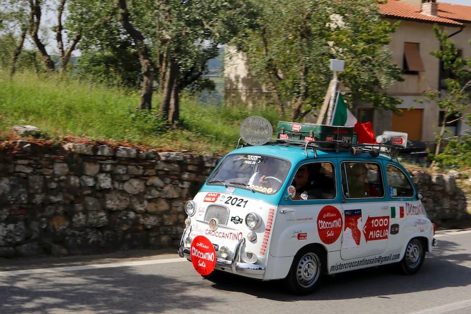 最後尾を走りながら沿道の観客にお菓子を配るフィアット・ムルティプラ(1962年)。参加車ではありませんが、その愛らしい姿は毎年レースを盛り上げます