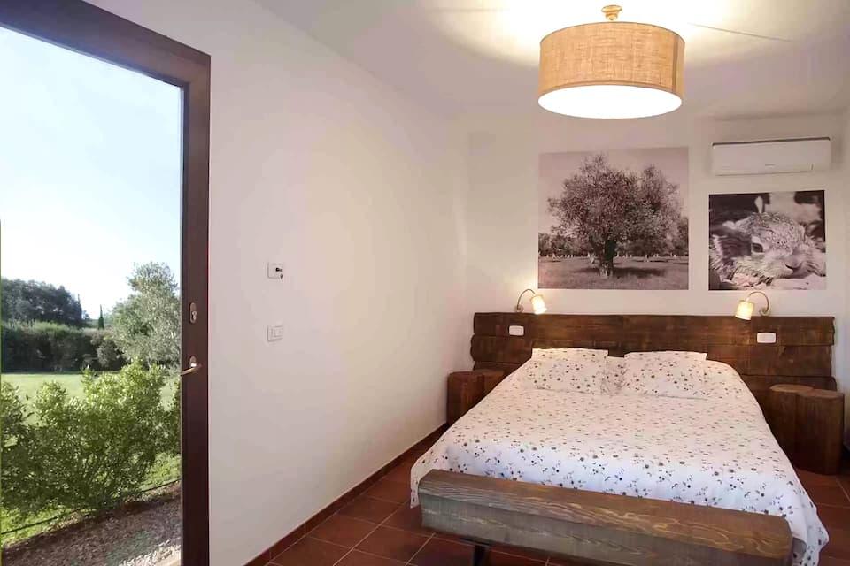 田舎風のダブルルーム。天然の蜜蝋が塗られた家具から、優しい香りが漂います。(photo: Corte degli Ulivi)