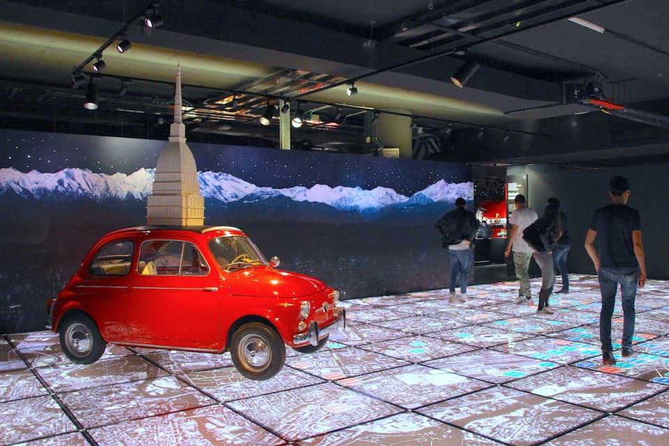 トリノのランドマーク「アントネッリの塔」を載せたFIAT500(1962年)は、イタリア第7代大統領サンドロ・ペルティーニが所有していたもの。フロアには航空写真が敷き詰められ、市内各地にあった歴史的カロッツェリア(車体制作工房)の所在地が記されています。